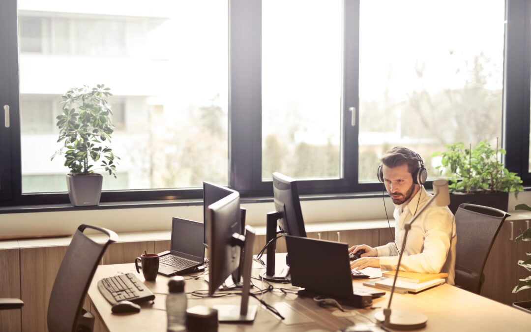 man with headphones facing computer monitor 845451 scaled